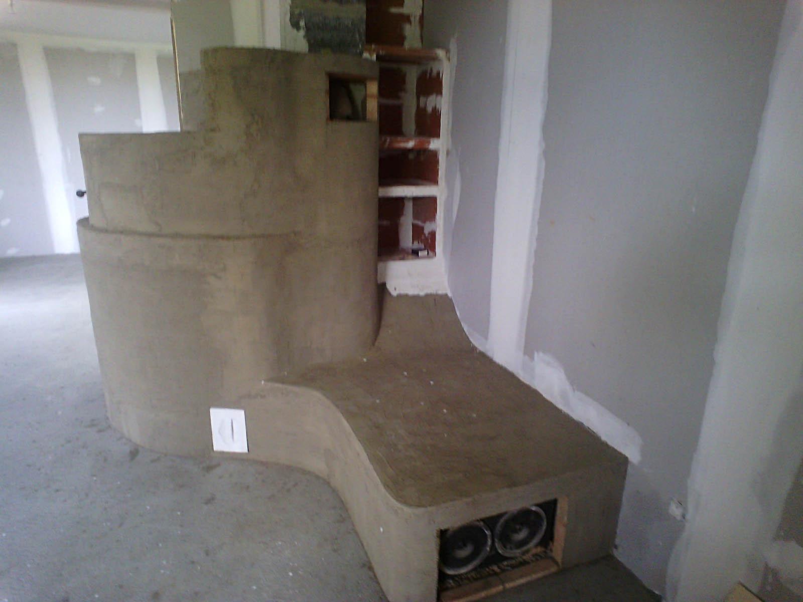Création d'un poêle de masse avec étagères intégrées dans le coin de lecture chauffé et illuminé
